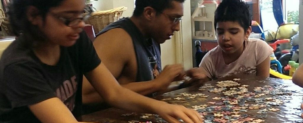 Family of two young girls and young male putting a puzzle together at a table