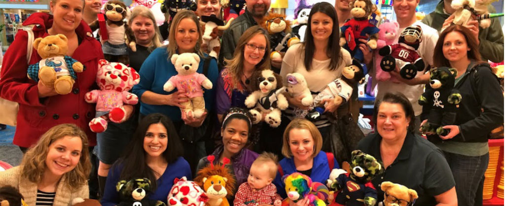 Young professionals posing with teddy bears inside a build-a-bear workshop