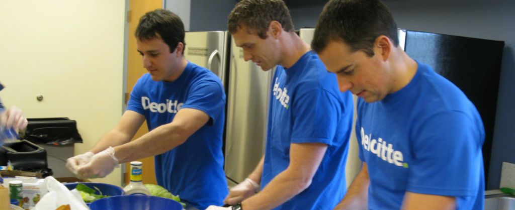 Three men wearing the same company shirt cook a meal at the Ronald McDonald House
