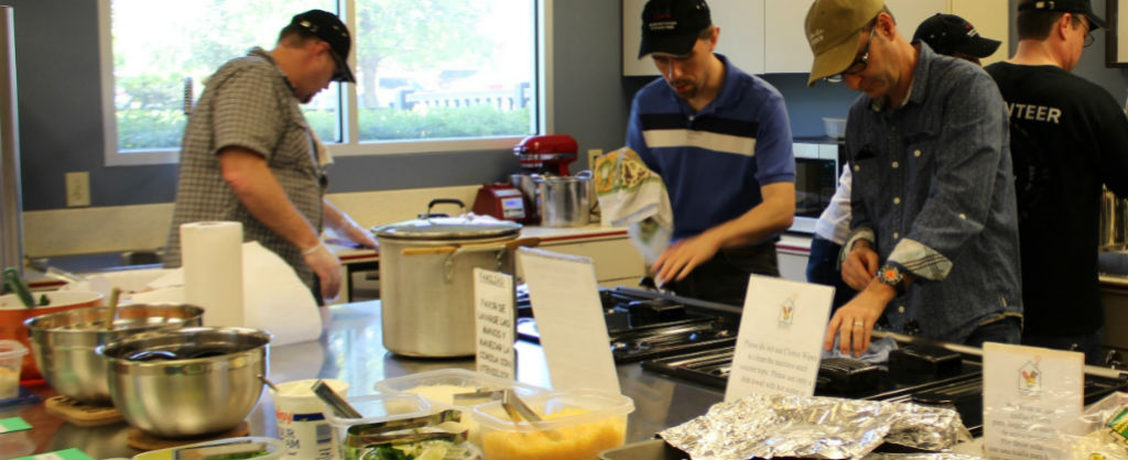 Group of men diligently cooking at the Ronald McDonald House