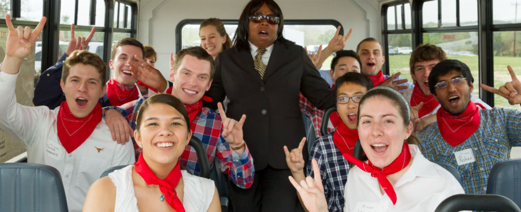 """Group of college students show all raise their hands in a hand signal to indicate """"hook em horns"""" on a bus while dressed with the same red bandana around their necks"""