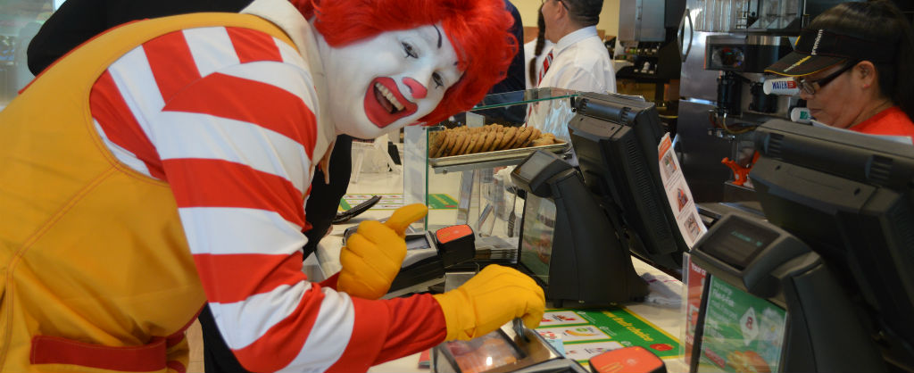 Ronald McDonald puts change in a McDonald's change box and smiles with a thumbs up at the camera