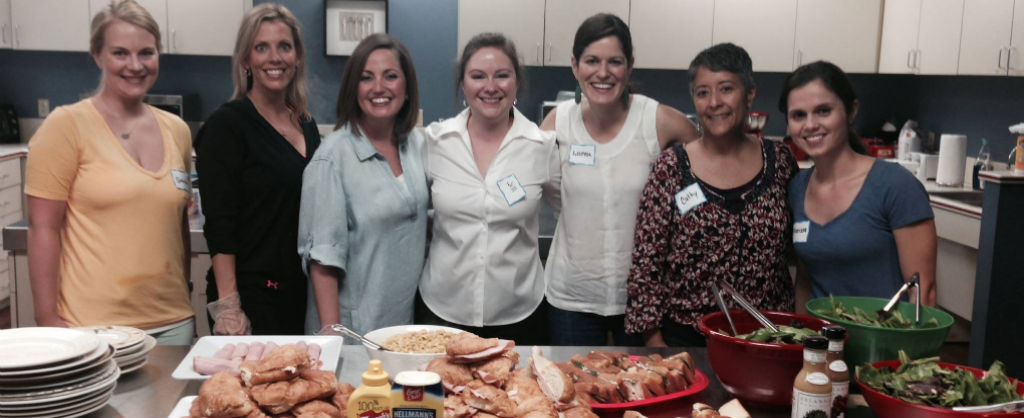 Group of women posing in kitchen behind spread of dinner at the Ronald McDonald House