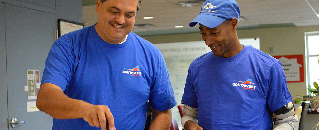 Two men are smiling and wearing Southwest airline outfits as they prepare a meal for the Ronald McDonald House.