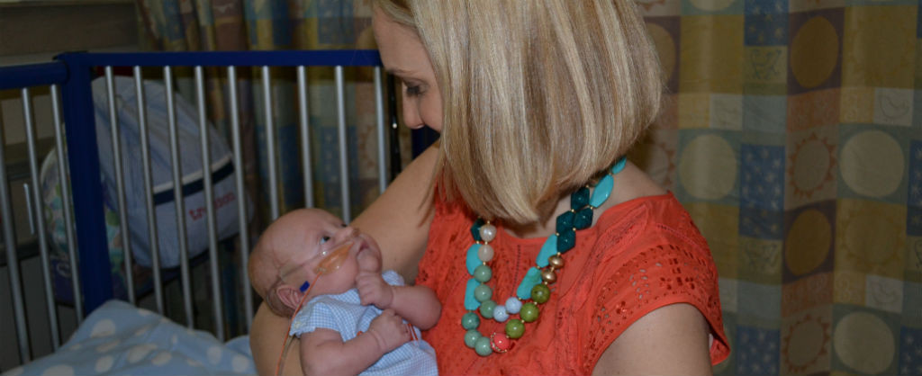 Mother smiling down at her tiny baby with breathing tube in her nose inside a hospital room