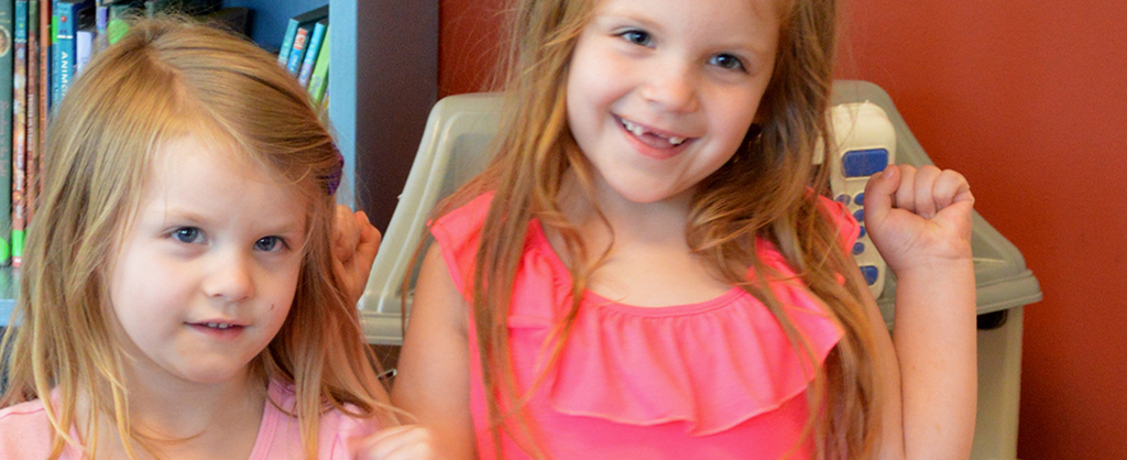 Two sisters look at camera and smile in the playroom at the Ronald McDonald House!