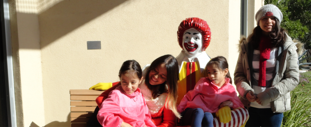 Mom and twins sitting on bench with statue of Ronald McDonald and smiling while older daughter stands next to statue.