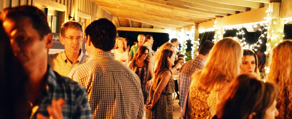 Crowd of people conversing on a patio at night with bright strings of light bulbs displayed throughout patio beams