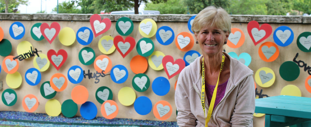 Charlie the volunteer smiles while sitting in front of a colorful wall outside of the Ronald McDonald House.