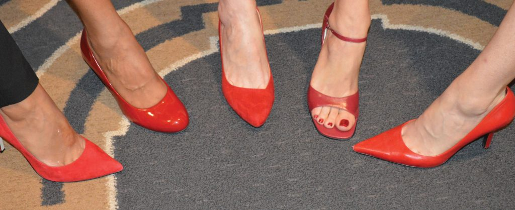 5 unique feet inside fancy red shoes in semi circle