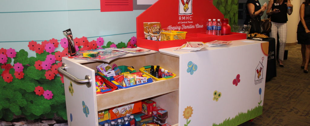 Happy Wheels Cart with drawers pulled out and stocked with snacks and beverages, as well as stocked on top. The Cart is decorated with stickers of flowers and butterflies. Behind the cart is a colorful wall paper and a group of women in the background to the right.