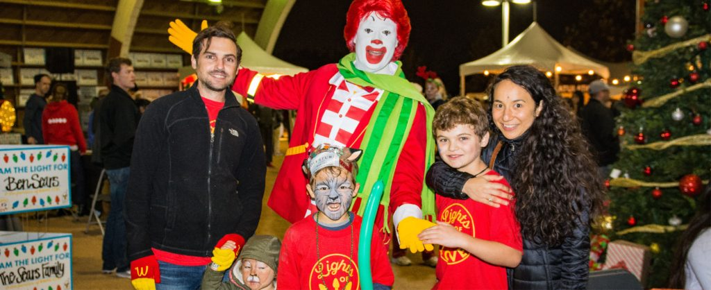 From left, man with a black jacket, Ronald McDonald wearing red jacket, red and white stripped shirt, green scarf and yellow gloves with young boy with a painted face and red t-shirt holding a green balloon in front of Ronald; young boy with red tshirt to the right of Ronald and woman with long dark wavy hair and black jacket with her arm around young boy