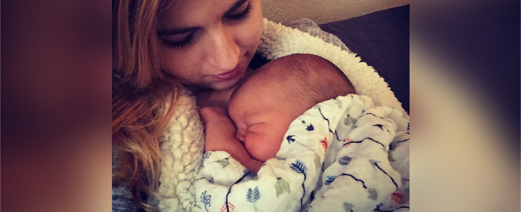 Mom with long hair cradling newborn next to her chest