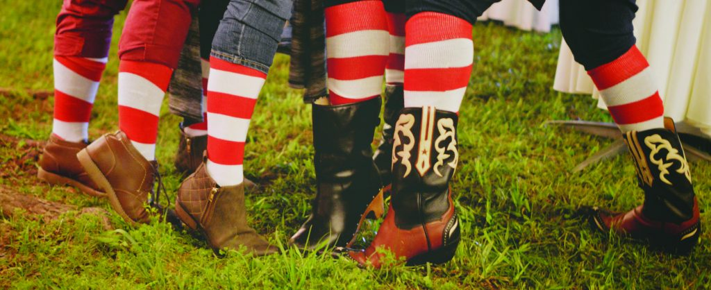 Close up of four people's legs and and shoes on grass. Legs are displaying red and white striped socks