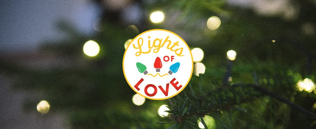 Lights of Love Logo over background of close up of white christmas lights in a tree