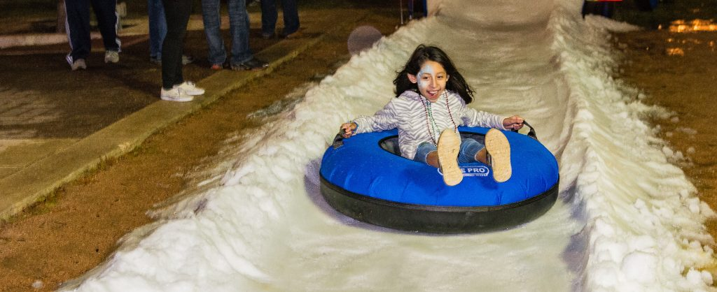 Little girl slides on a tube down a snow slide with excitement at Lights of Love event
