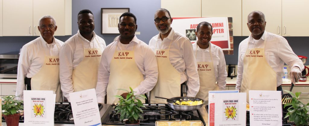 Fraternity Alumni group pose while cooking breakfast at the Ronald McDonald House.