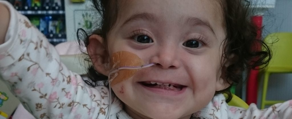 Toddler Elena is smiling with arms wide open in a hospital setting