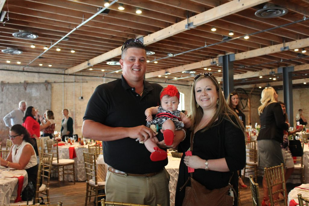 The Janda family from left to right, smile and hold their baby girl at Brazos Hall.