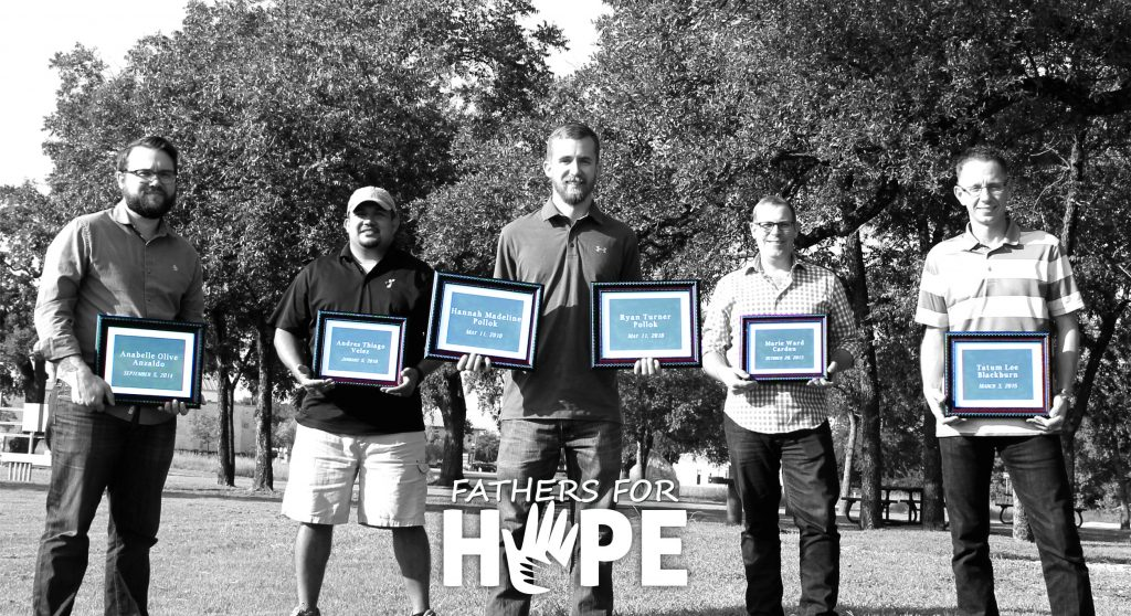 Fathers for Hope Group stand in a row holding frames honoring their late children.