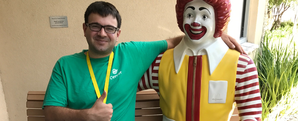Volunteer Trevor happily poses with a statue of Ronald McDonald and has his hand in a thumbs up gesture.