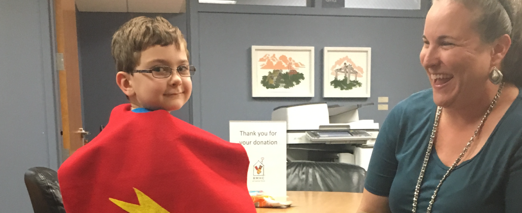 Young boy looks back over his shoulder while wearing a cape. Mom is sitting next to him and smiling at him.