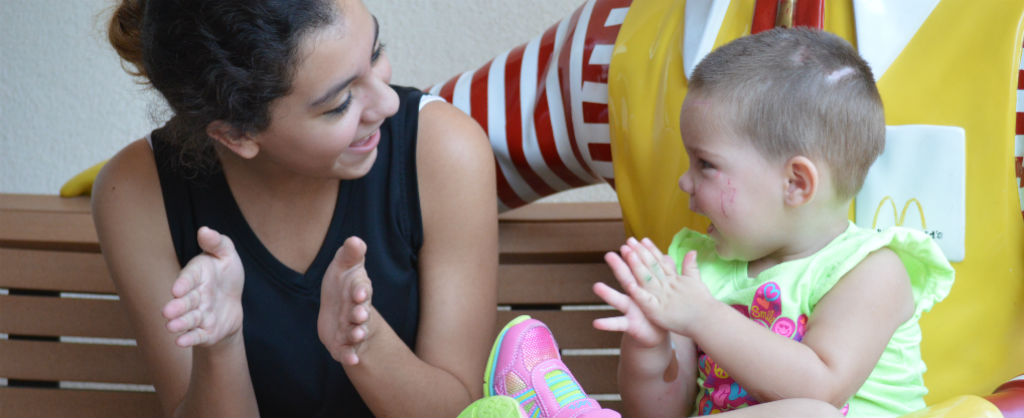 Teenage girl and toddler girl sit together and laughing while playing a clapping game
