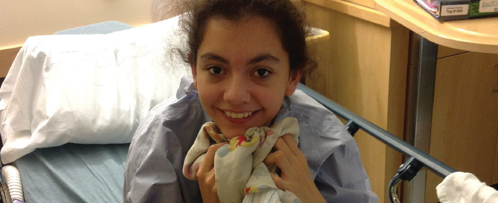 Caylie Brown holding a child's blanket and smiling into camera while sitting up in her hospital bed