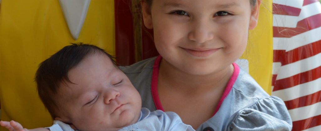 Young girl holds her sleeping baby brother in her arms and sits in the lap of the Ronald McDonald statue.