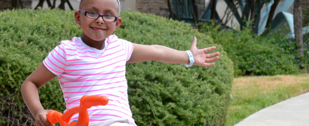 Young girl Kaylee smiling with her arm spread out in the front yard of the Ronald McDonald House.