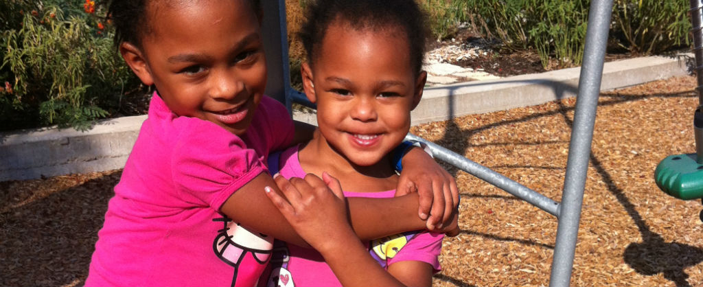 Two sisters holding each other outside on a playground and smiling