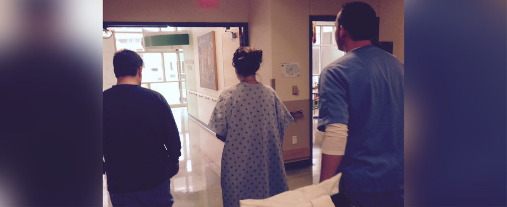 The back of a young girl in a hospital gown with a man to her left in a black shirt, and a medical staff person in blue scrubs on her right pulling a piece of equipment. All are walking down a hospital hallway. There are blurred versions of the image on the right and left sides of the main image