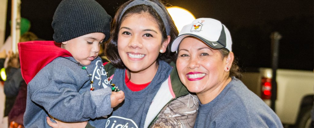 From the left, toddler wearing a black knit cap with a gray sweatshirt held by a woman with dark hair, gray headband and gray sweatshirt next to a woman with a red and black Ronald McDonald House Charities ball cap and gray sweatshirt