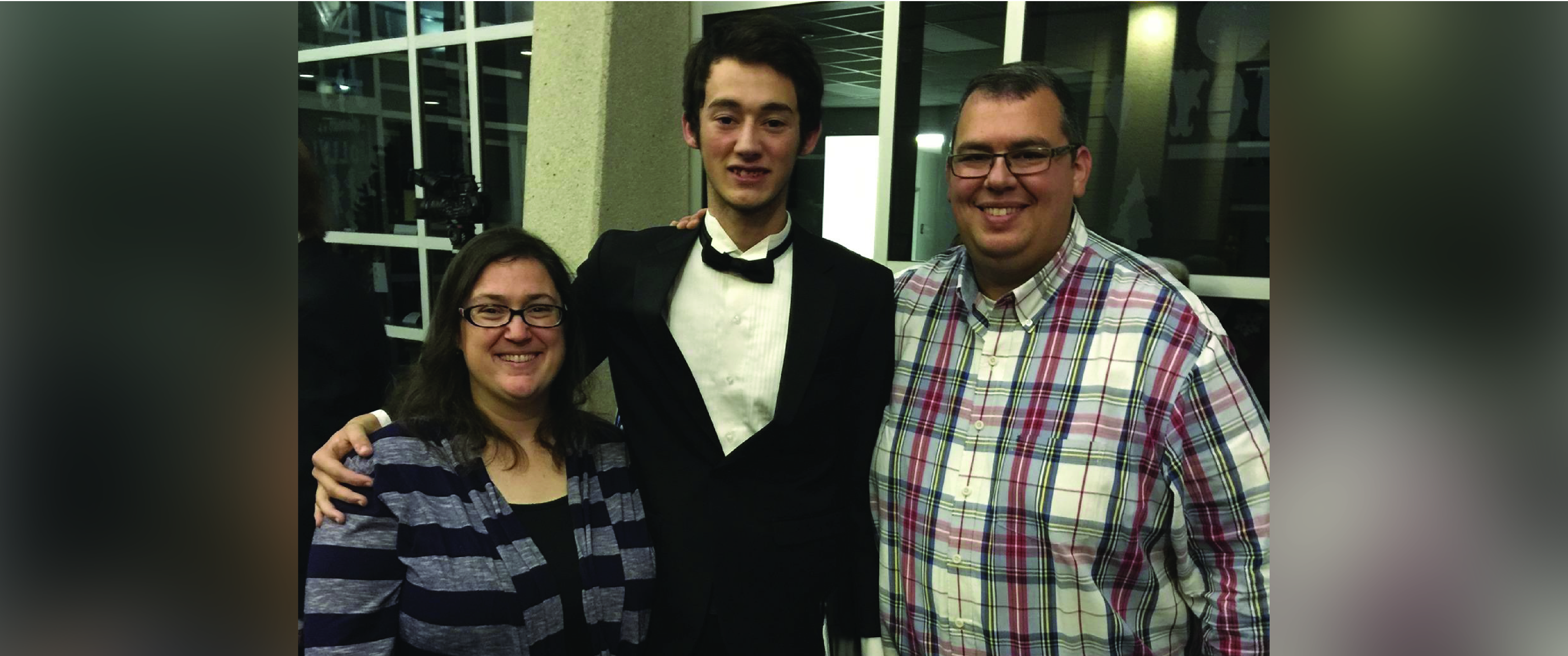 From left, mom with striped shirt, son wearing a tuxedo, dad wearing a plaid shirt