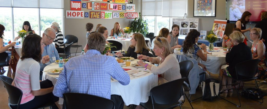 Members of the Red Shoe Society eat together at round tables in the community room at the Ronald McDonald House