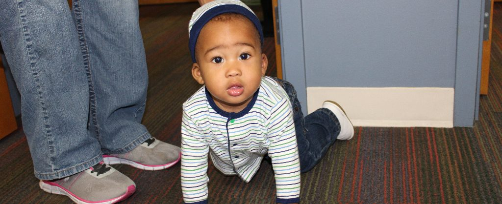 Baby Wyatt looks up at the camera while crawling on the floor of RMHC CTX office