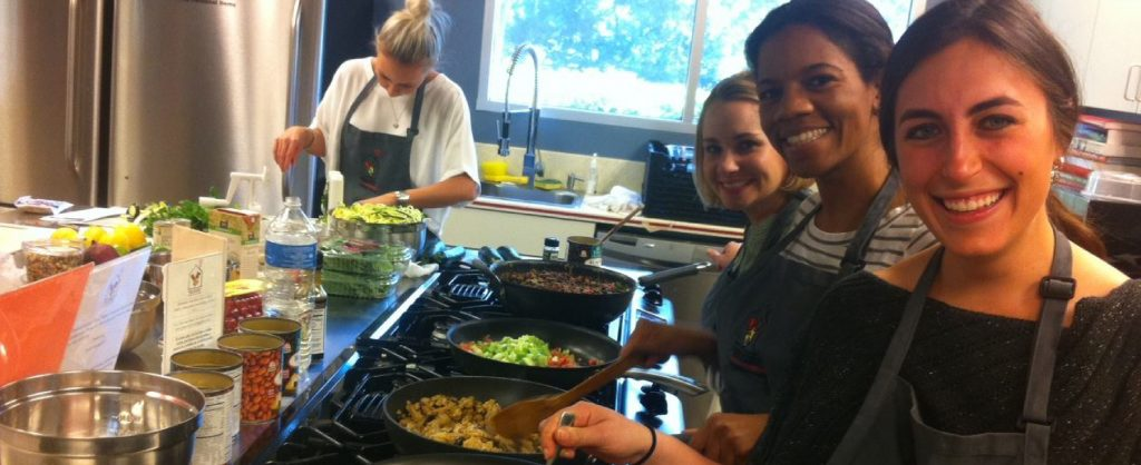 Young women smile and cook a meal for the families at the Ronald McDonald House