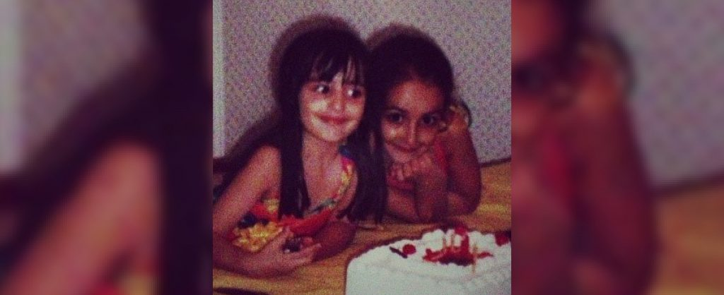 Lauren and her sister smile and pose in front of a birthday cake from the early 1990s