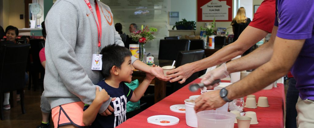 Little boy smiles up at volunteers from Lick Honest Ice Creams as they scoop him some ice cream