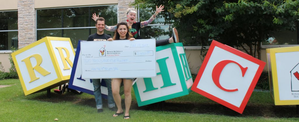 Three enthusiastic fundraisers present a giant check in front of the colorful RMHC blocks