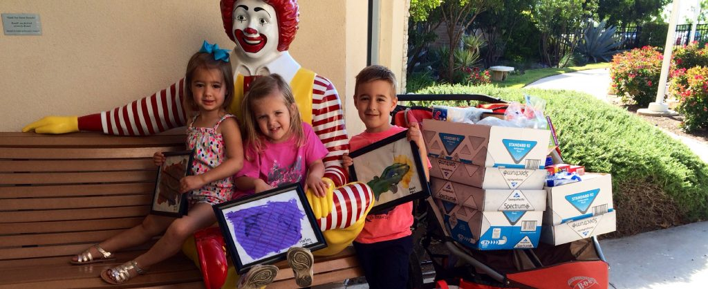 Three young children smile and hold artwork they made for RMHC and pose with wish list items they are donating.