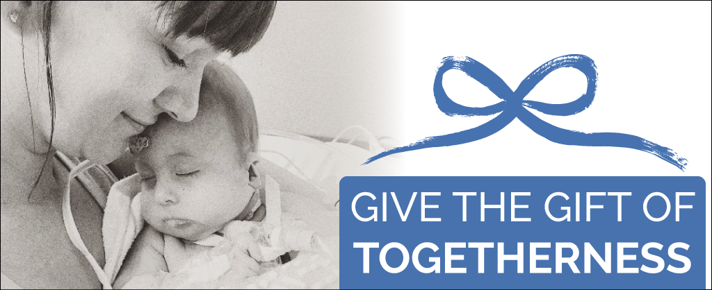 "Krystal smiles down on a sleeping baby gus, ""Give the Gift of Togetherness"" is overlaid inside a blue present graphic."