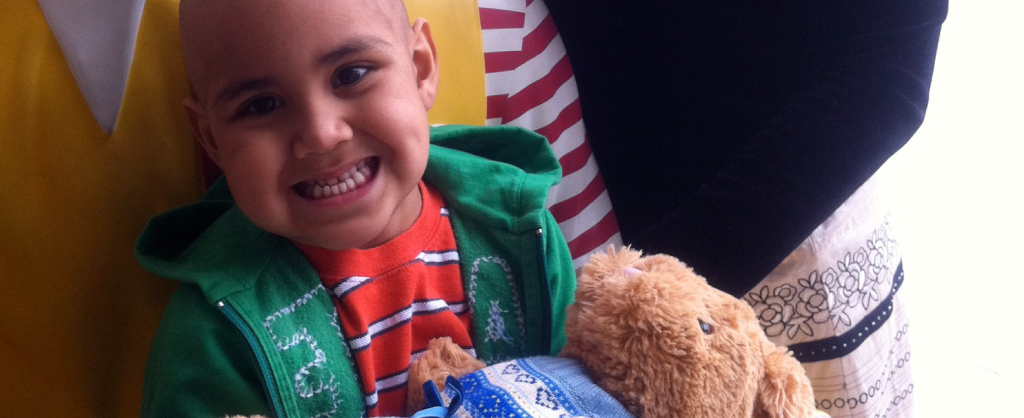 Nicholas smiles wide and holds his stuffed teddy bear at the Ronald McDonald House.