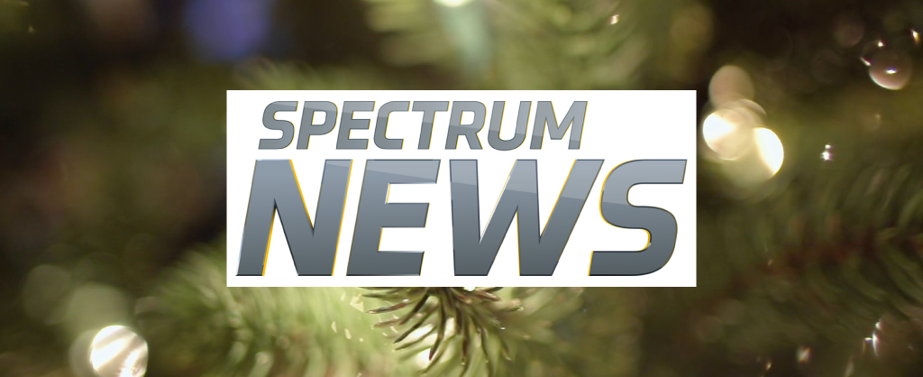 Spectrum News logo on a backdrop of blurry Christmas lights