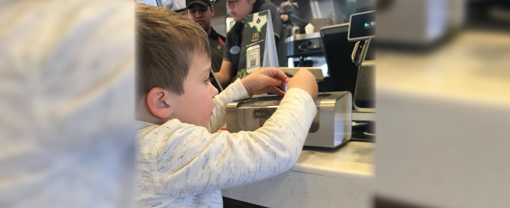 young boy donating money to change donation box at mcdonalds restaurant