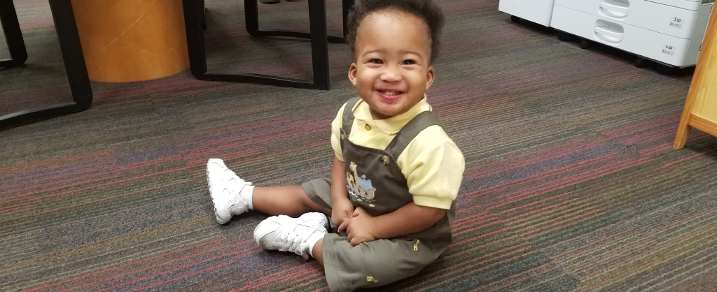 Baby Wyatt sits on the floor and smiles up