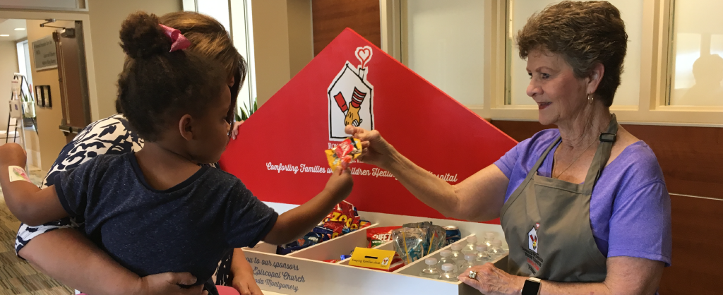 A Volunteer hands a small child a snack from the Happy Wheels Cart inside a Central Texas hospital.