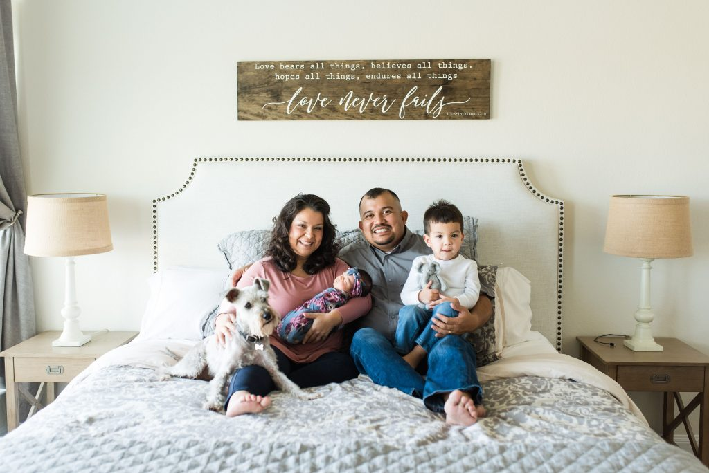 Dog, mom holding baby, dad holding son sitting on a bed