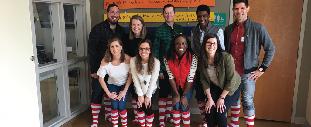 members of friends of the house smiling together for a group photo with matching red and white striped socks