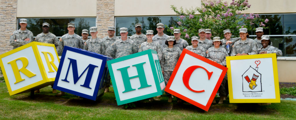 """group of military personnel volunteering as a group and posing behind large child-like blocks spelling """"RMHC"""""""